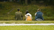 Three teenage friends sitting on the shore of the pond in the park, rear view Stock Footage