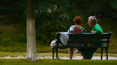 Two elderly women are talking, sitting on a bench in the park Stock Footage