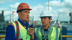 Industrial workers controls work in a factory with walkie-talkie Stock Footage