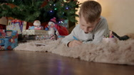 Little boy lying under christmas tree and drawing letter to santa claus Stock Footage