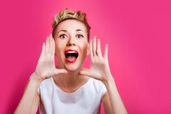 Pretty woman shouts on the pink backdrop concept Stock Photos
