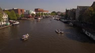 Aerial. Tour boats on water channel in Amsterdam. Camera moves back. 4K Stock Footage