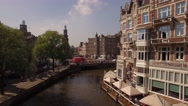 Aerial. Tour boats on water channel in Amsterdam. Camera moving up. 4K Stock Footage