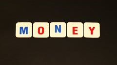 Word MONEY on black background. Stop motion Stock Footage