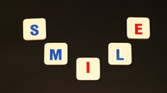 Word 'smile' layed out from letters in form of a smile. Stop motion Stock Footage