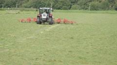 Farmer in tractor turning hay,Oudekerk,Netherlands Stock Footage