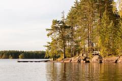 Nordic lake landscape of a wooden dock at a rocky shore with pine trees Stock Photos