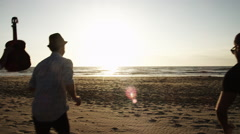 Group of youngsters running on beach to sundown Stock Footage