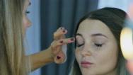 Beautiful girl doing makeup Stock Footage