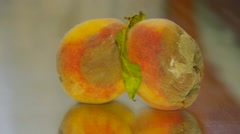 Couple rotten peach lies on the mirror table, close-up Stock Footage