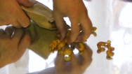 Man collects cashew nuts on the table in a paper bag, close-up Stock Footage