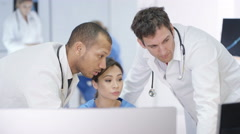 4K Medical team in modern hospital looking at computer & having a meeting Stock Footage