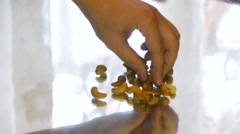 Man eating cashew nuts lying on a mirror table, close-up Stock Footage