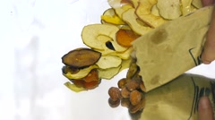 Someone pours almonds and cashews near the dried fruits of apples Stock Footage