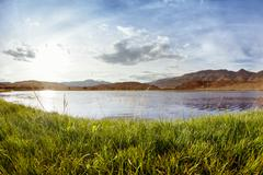 Crystal lake and grass on the montains backgroud. Altay Stock Photos