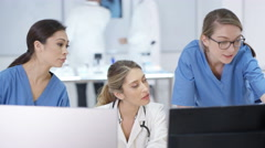 4K Female medical team in modern hospital looking at computer & having a meeting Stock Footage