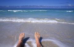 Man's feet on edge of Carribean Sea at Cancun Mexico Kuvituskuvat