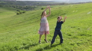 Two kids catch the soap bubbles on the hill Stock Footage
