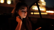 Beautiful girl riding in a taxi at night and wrote a message on the phone Stock Footage