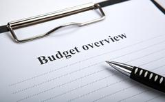 Document with title budget overview and pen Kuvituskuvat