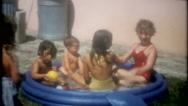 Children crowd into small pool to cool off- 3627 vintage film home movie Stock Footage