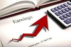 Table with earnings with digits, calculator and diagram Stock Photos