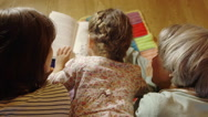 Girl with mother and grandmother reading book Stock Footage