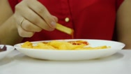 Girl in red eating fries hands, close-up Stock Footage