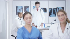 4K Portrait smiling doctors in modern clinic, colleagues working in background Stock Footage
