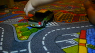 A child pushes a button on a toy car, and it starts to go, close-up Stock Footage