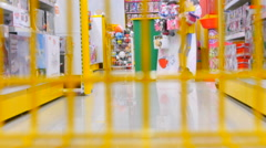 Someone goes to the shopping cart through the store children's toys Stock Footage