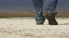 Man walking on dried salt lake under a blazing sun Stock Footage