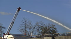 Fireman fighting fire spraying water from the hose while on top a ladder Stock Footage