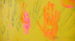 Multicolored prints of hands on the yellow wall, close-up Stock Footage