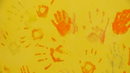Multicolored prints of hands on the yellow wall, panorama from left to right Stock Footage