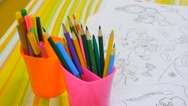 Set of pencils and felt-tip pens in cups near coloring books Stock Footage