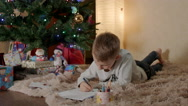 Blond boy lying under the christmas tree, and writing a letter to Santa Stock Footage