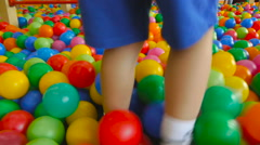 Little boy playing in the paddling pool filled with colorful balls Stock Footage