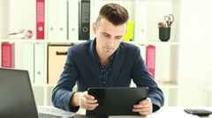 Businessman Playing games in the office using a tablet and wins Stock Footage