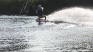 Blonde rides on a wakeboard raising splashes, slow motion Stock Footage