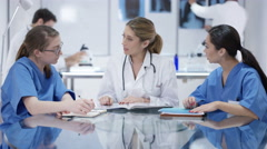 4K Female medical team in a meeting with male colleagues working in background Stock Footage