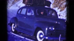 1946: a man freezing inside his 1950's purple vehicle with white wall tires. Stock Footage