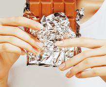 Woman eating chocolate, close up hands with manicure french nails holding candy Stock Photos