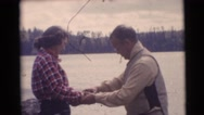1953: man teaching a young woman how to cast a fishing line in the water Stock Footage