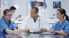 4K Medical team in a meeting with colleagues working in background Stock Footage