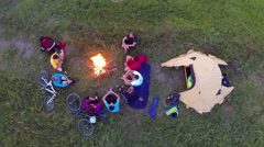 Aerial: Group of campers sitting around the camp fire and talking. Stock Footage