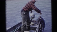 1953: a man standing upright in a boat, pulls lots of stringed fish Stock Footage