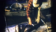 1953: the man puts fishes into the thread bag WISCONSIN Stock Footage