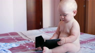 Cute kid sitting on the bed and stares cartoons on the tablet PC. Tiny one-year Stock Footage