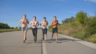 Young strong muscular guys exercising on rural road together. Slow motion Stock Footage